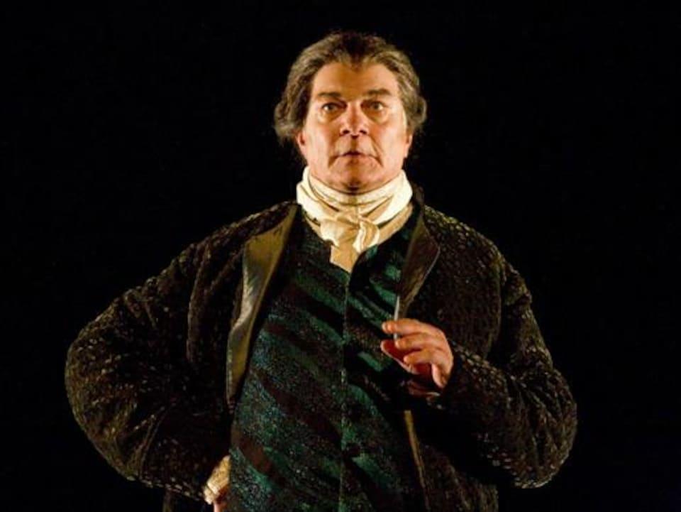 Un homme portant une perruque et un costume du 18e siècle s'exprime sur une scène de théâtre.