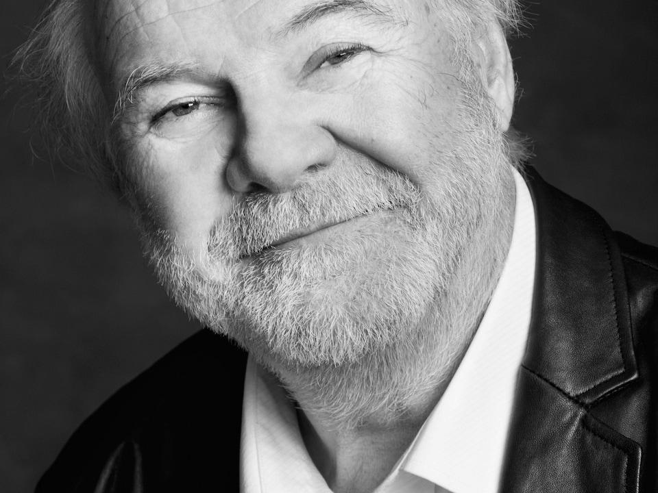 Retrato en blanco y negro de Michel Noël, que lleva una barba blanca.
