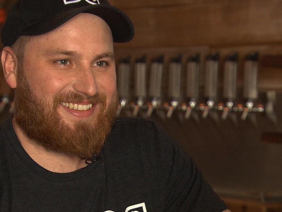 Keegan Kelertas sourit lors d'une entrevue dans une microbrasserie.