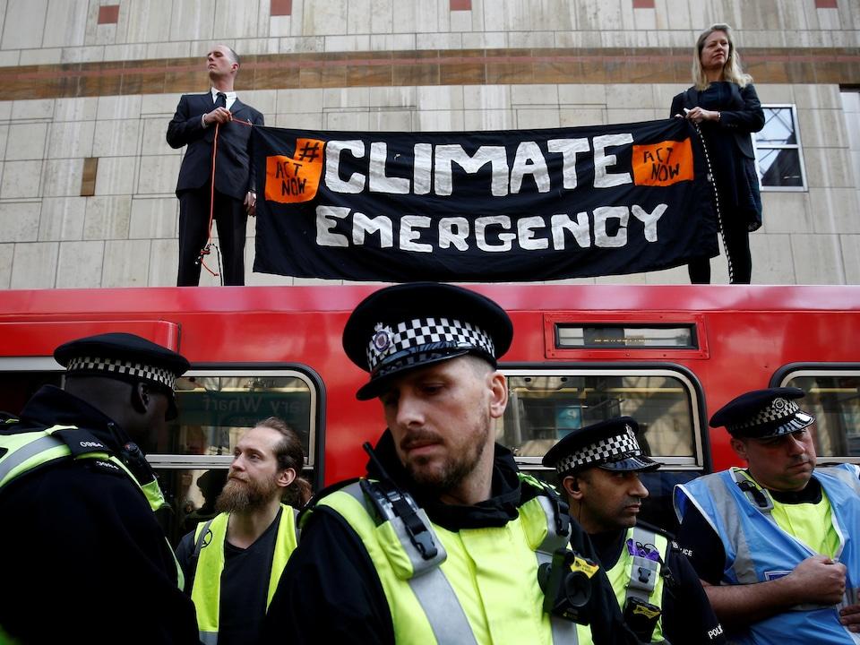 Un policier surveille un train sur lequel des manifestants tiennent une banderole.