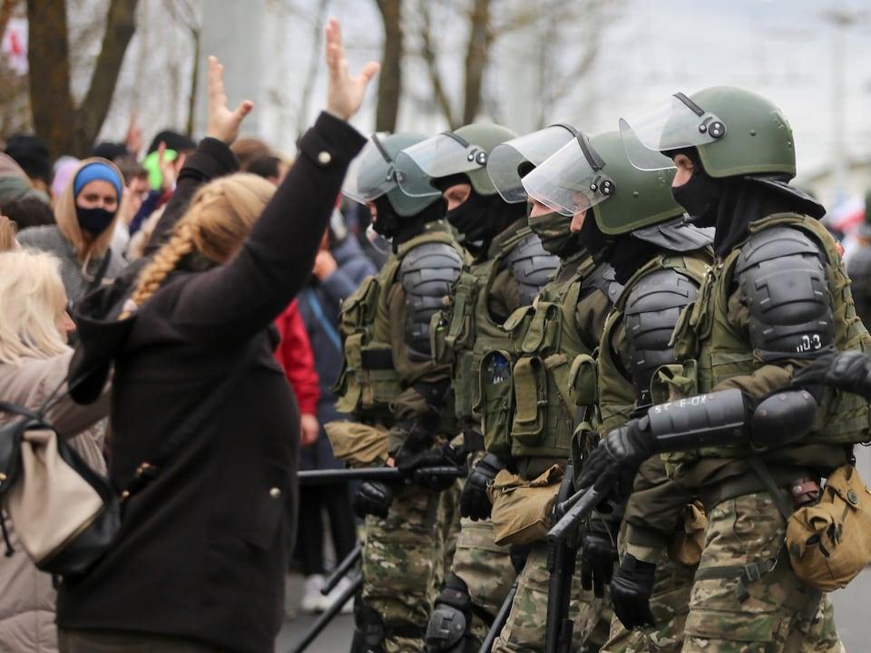 Une manifestante, les bras en l'air, fait face à des policiers armés et casqués.
