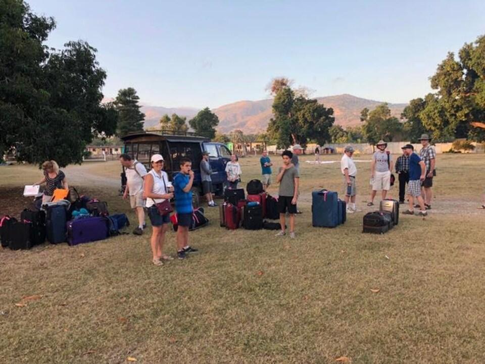 Des gens attendent au milieu de valises dans un parc. Ils sont souriants.