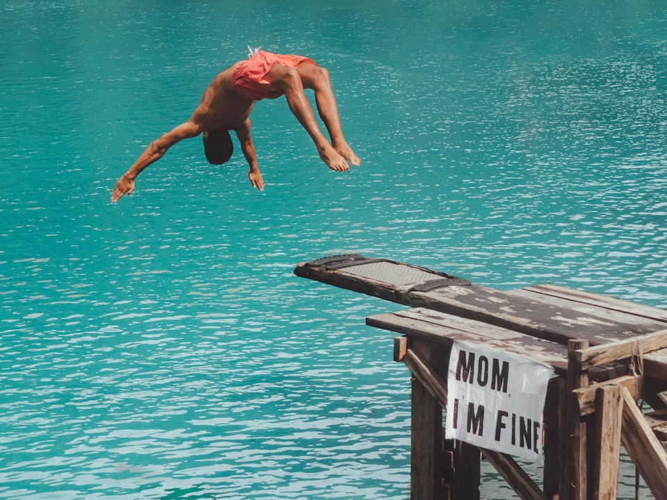 Jonathan Kubben effectue un plongeon dans une eau turquoise avec sa pancarte Mom I'm Fine fixée sur le tremplin.