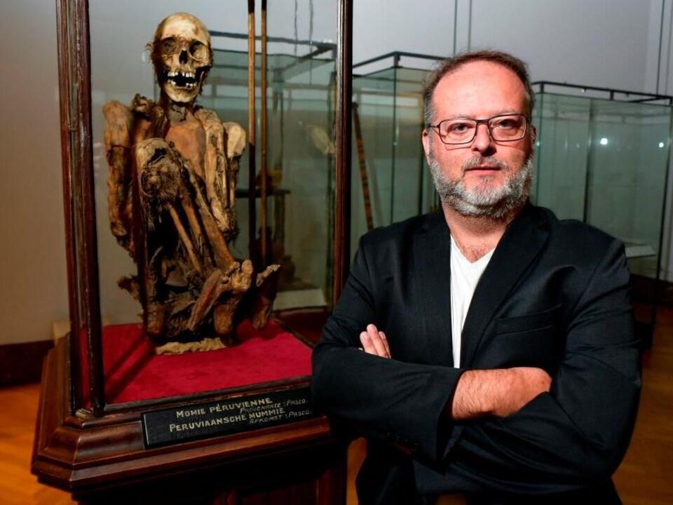 Un homme portant une veste noire et des lunettes se tient debout près d'une momie.