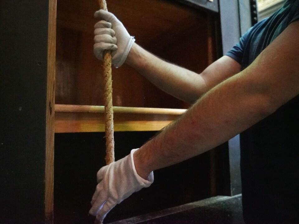 Un homme ganté de blanc tire sur une corde.