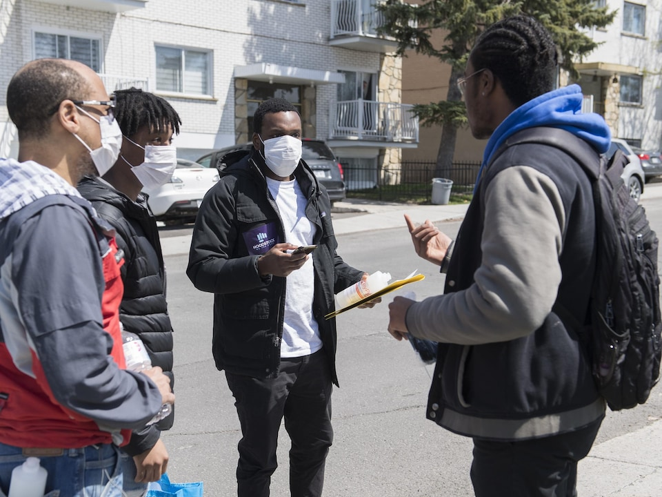 Trois bénévoles discutent avec un passant.