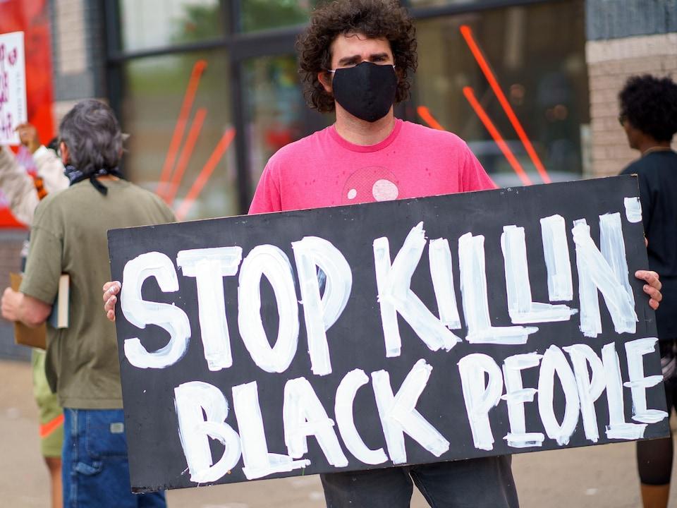 Un homme porte une pancarte sur laquelle on peut lire : « Stop killin' black people » (Arrêtez de tuer les Noirs).