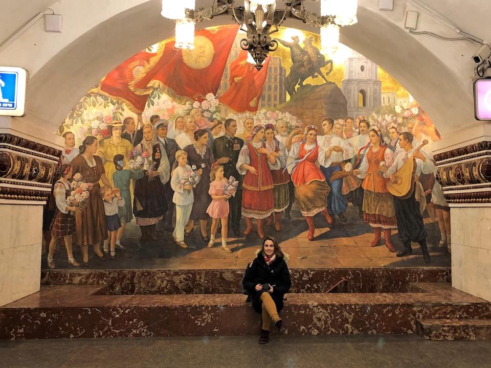 Notre journaliste, appareil photo à la main, est assise devant une grande fresque mettant en scène des personnages en costume folklorique ukrainien.