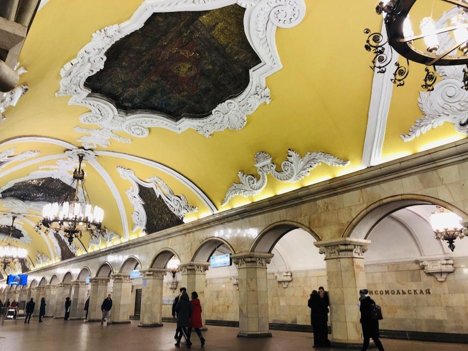 Quelques passants marchent dans l'allée centrale de la station Komsomolskaya, dont le plafond jaune aux moulures blanches est décoré de mosaïques sombres.