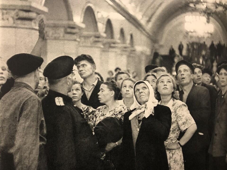 Détail d'une photo en noir et blanc d'Henri Cartier-Bresson, prise en 1954. On y voit un groupe de voyageurs admirer les décorations du métro.