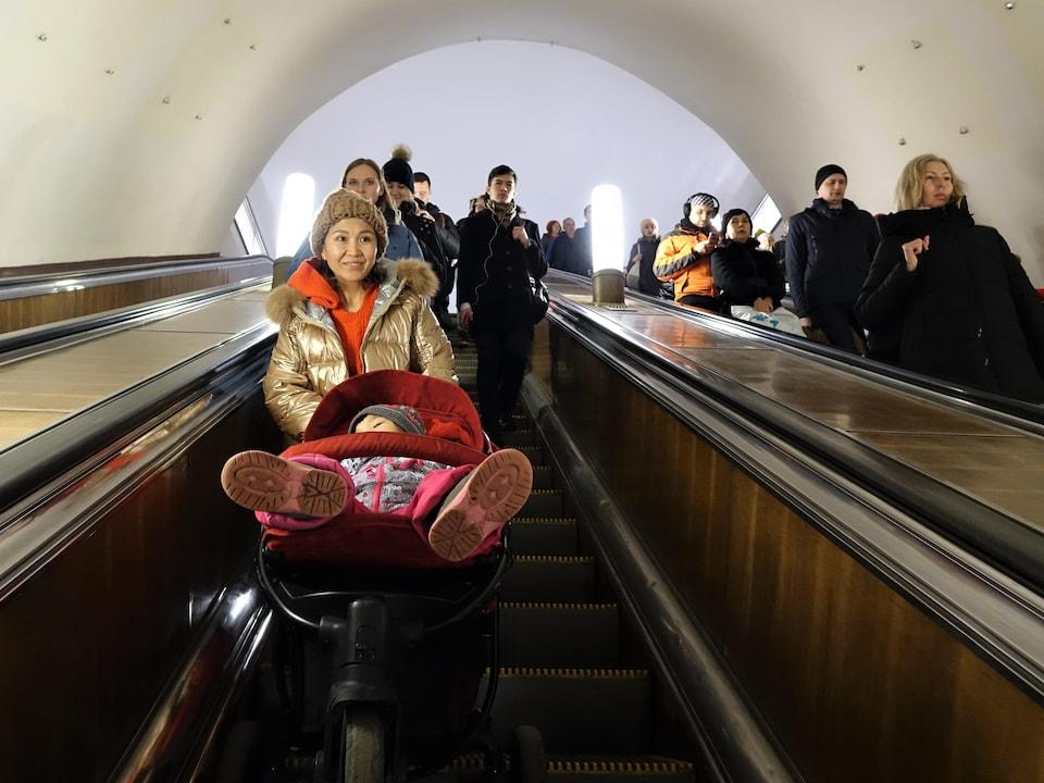 Une femme souriante avec son bébé endormi dans la poussette.