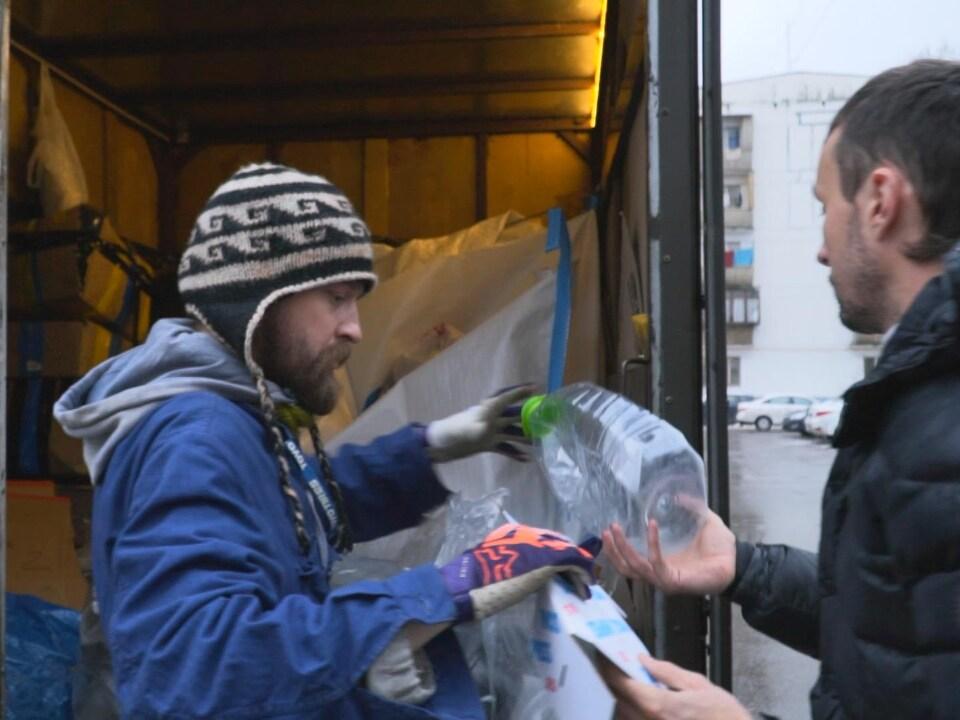 Un homme portant une tuque ramasse les matières recyclables que lui tend un autre homme pour les mettre dans son camion.