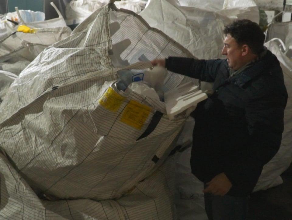 Un homme fouille dans un grand sac rempli de matières recyclables.