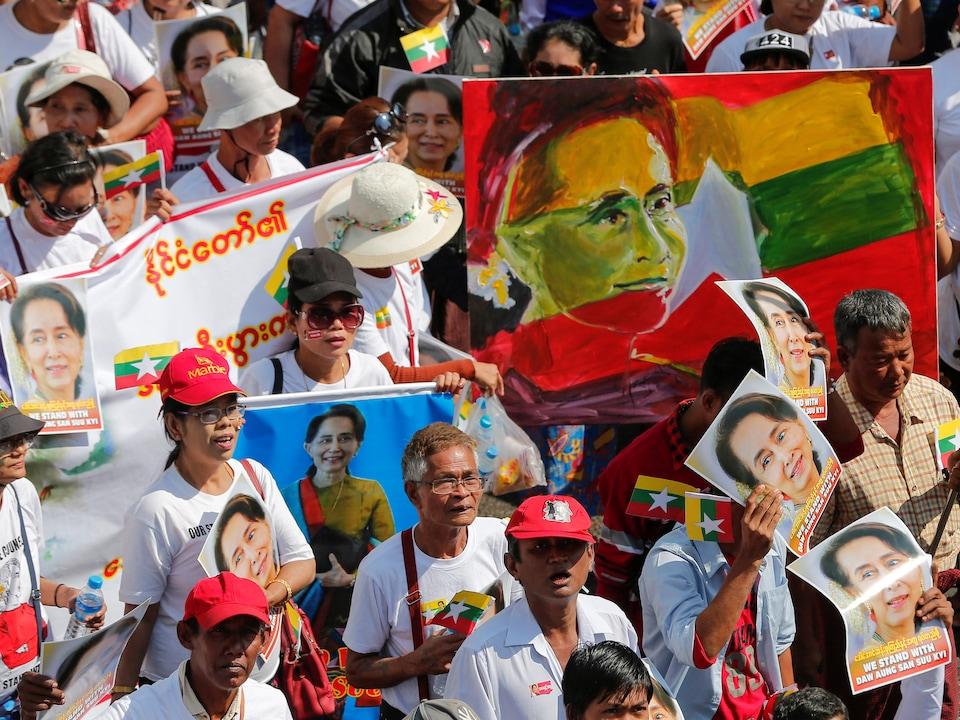 Des manifestants portent des photos de Mme Suu Kyi.