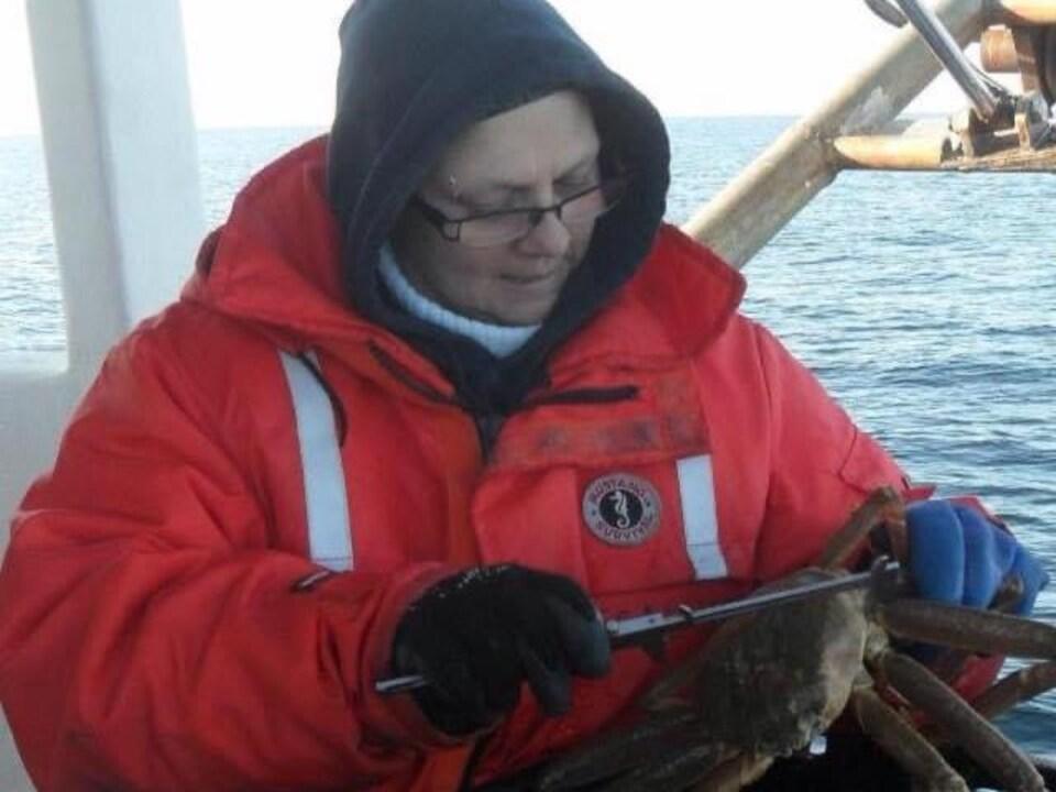 Nancy Bois en train de mesurer un crabe sur un bateau.