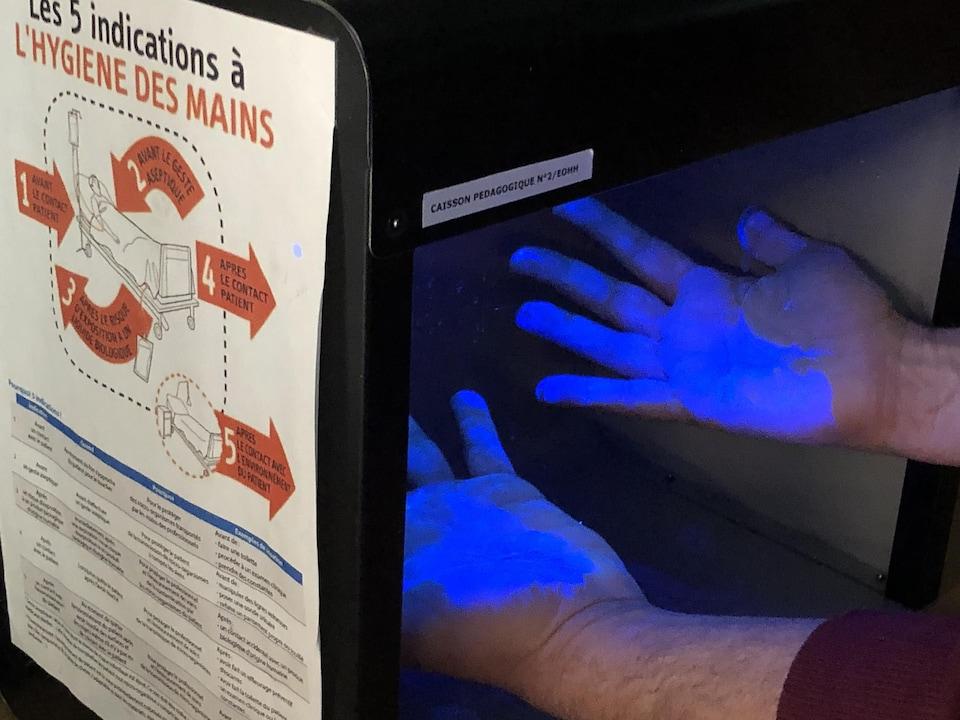 Des mains s'illuminent sous la lumière noire.