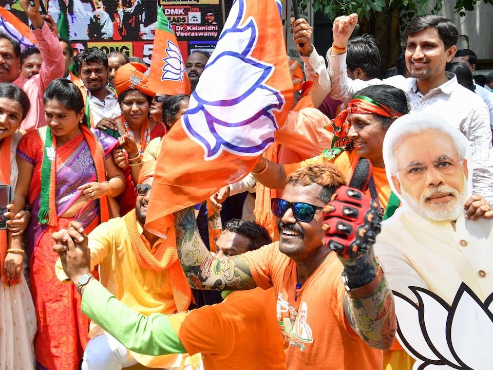 Des gens habillés de vêtements safran (couleur du BJP) agitent des drapeaux de leur parti.