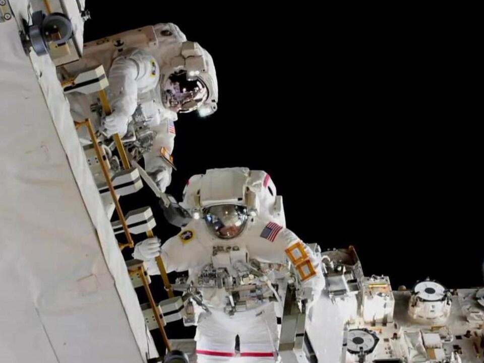 Les astronautes Nick Hague et Anne McClain procèdent à une sortie dans l'espace.