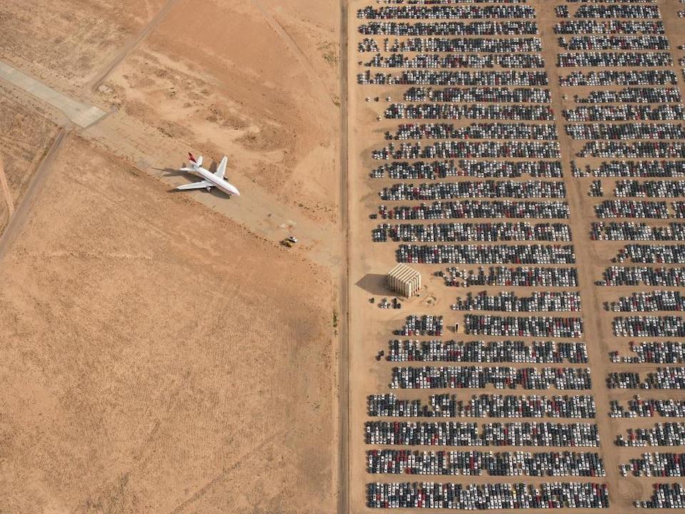 Un avion et des milliers de voitures Volkswagen et Audi stationnées dans le désert.