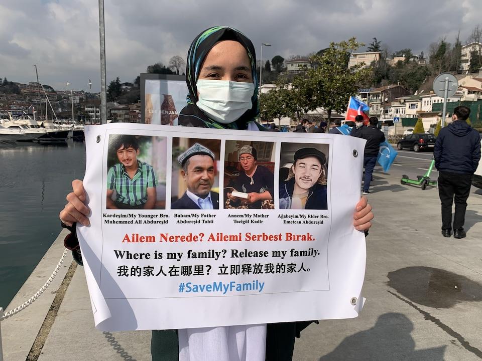 Nursimangul Abdurashid brandit une pancarte.