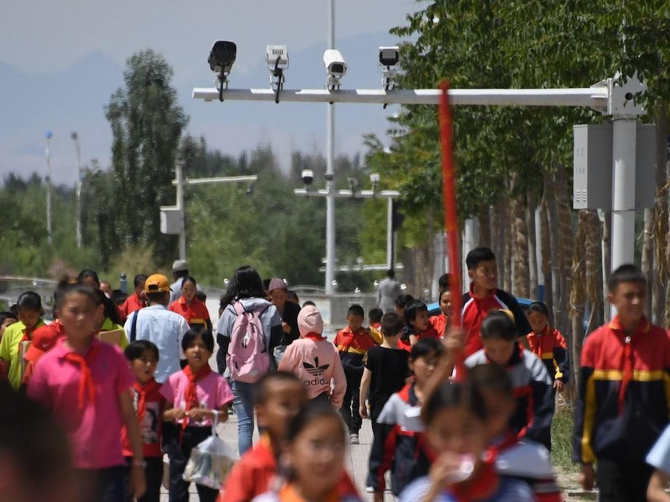 Un grand nombre d'enfants marchent sous plusieurs caméras de surveillance.