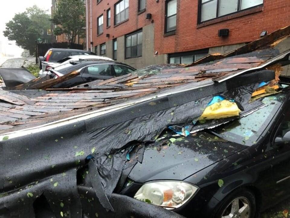 Des voitures sont écrasées par une toiture sous la pluie.