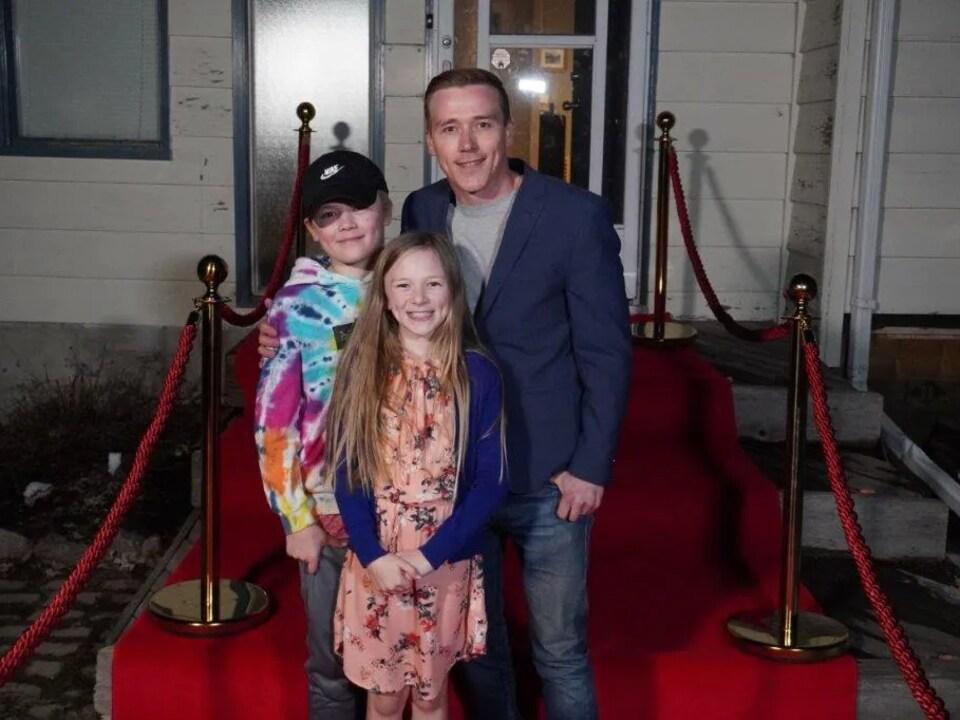 Paisley Cadorath avec son frère Kowen and son père Cory sur un tapis rouge.
