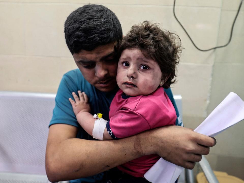 Un homme tient une fillette dans ses bras, les deux sont couverts de poussière.