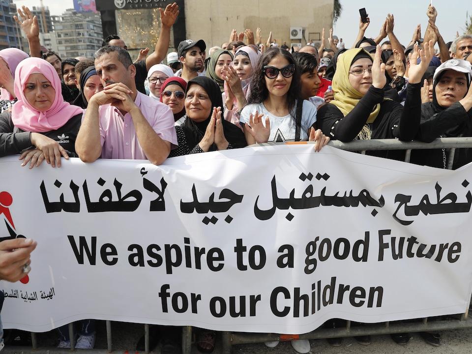 Des femmes et des hommes applaudissent lors d'une manifestation.