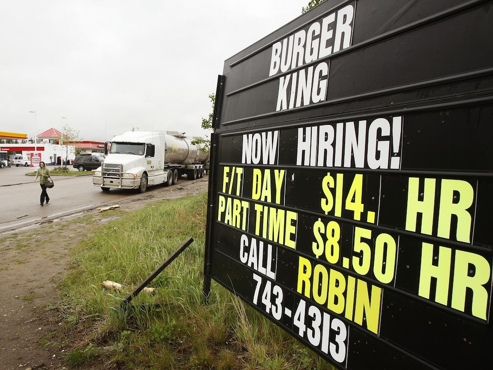 Une pancarte devant le restaurant Burger King à Fort McMurray en 2006. On peut lire : «On engage. Salaire de 14 $/h.»