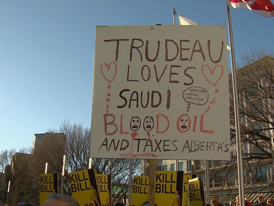 Une pancarte où il est écrit : « Trudeau aime le pétrole de l'Arabie saoudite, mais impose des taxes aux Albertains » est portée par un manifestant durant un rassemblement.