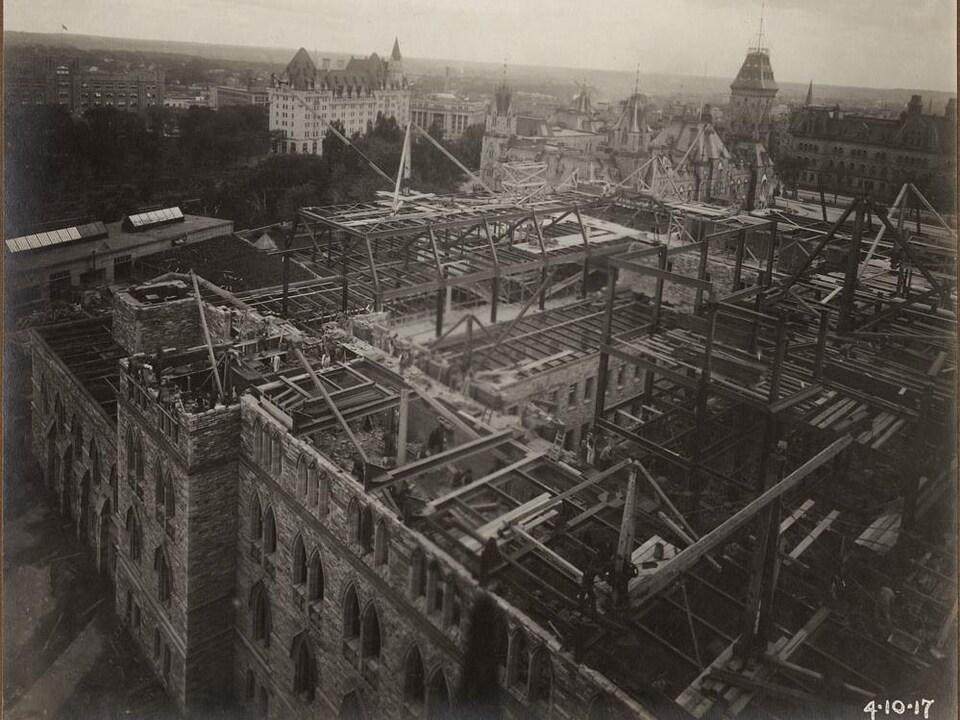 Vue en plongée au-dessus de l'édifice du parlement en reconstruction, en 1917. On voit la charpente des murs et du toit.