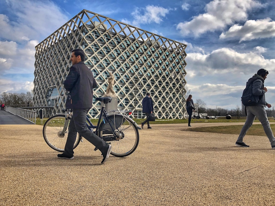 Un cycliste passe à pied devant un bâtiment à l'architecture originale.