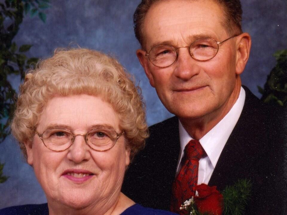 Plan serré de Percy Schmeiser (à droite) et de sa femme Louise. Ils regardent l'objectif en souriant et il porte une rose rouge à la boutonnière.