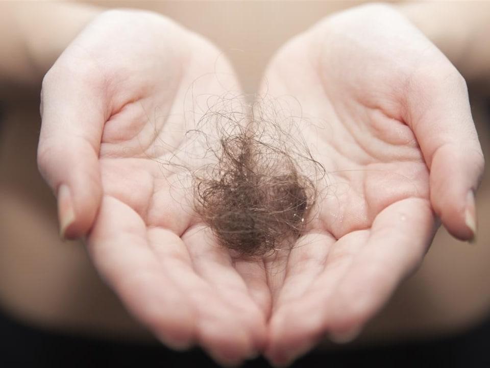 Une femme tient une boule de cheveux dans ses mains.