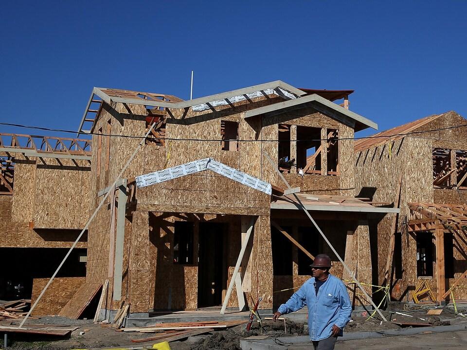 Un ouvrier passe devant une charpente de maison en bois.