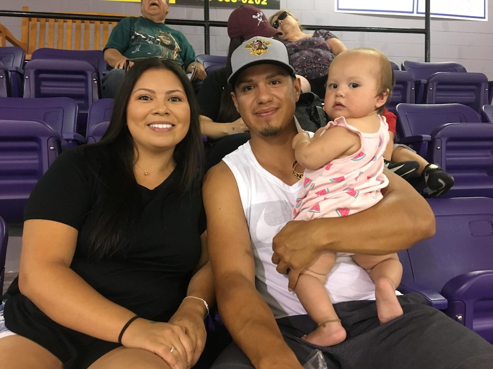 The young family sitting in the stands at the Kahnawake sports complex.
