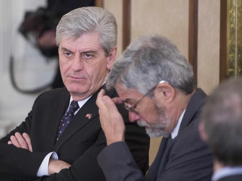 Un homme est assis les bras croisés avec un autre homme qui se gratte le front.