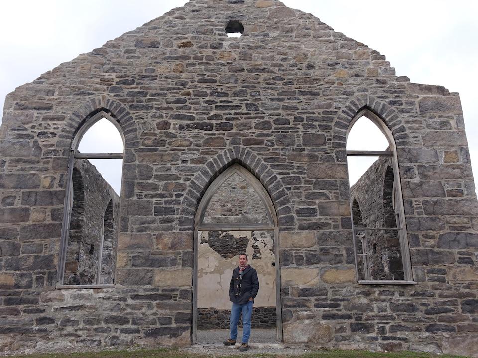 Plan large d'un homme sous le portail d'une église en ruine.