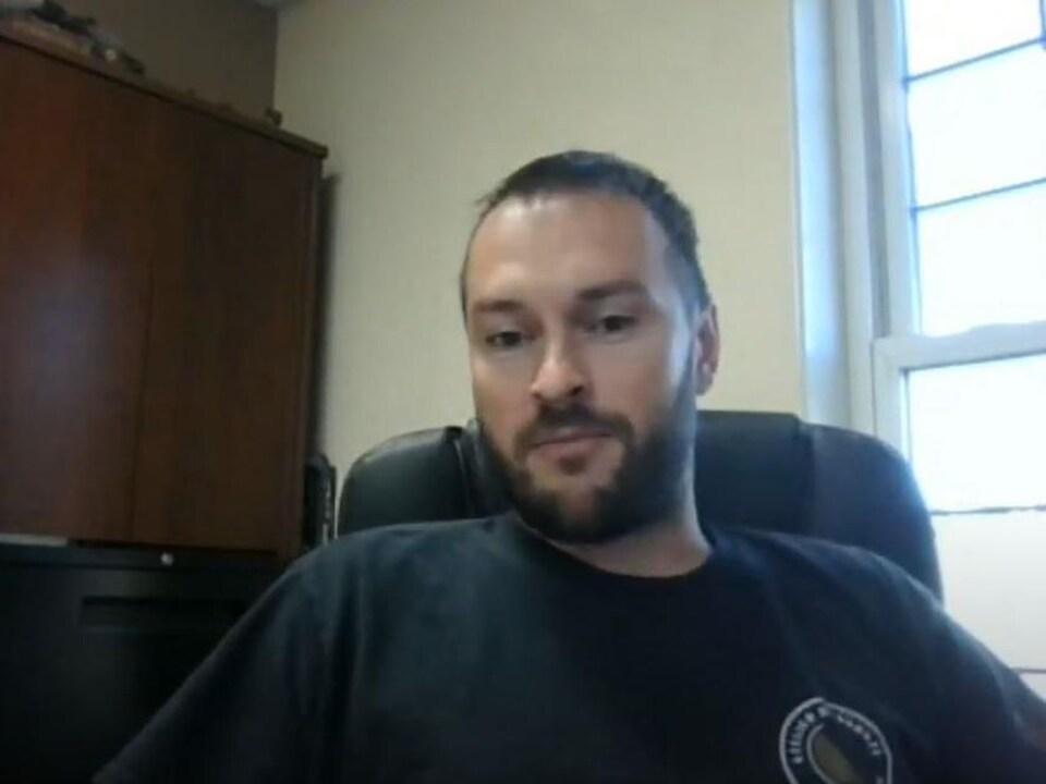Un homme barbu assis dans son bureau devant une fenêtre.