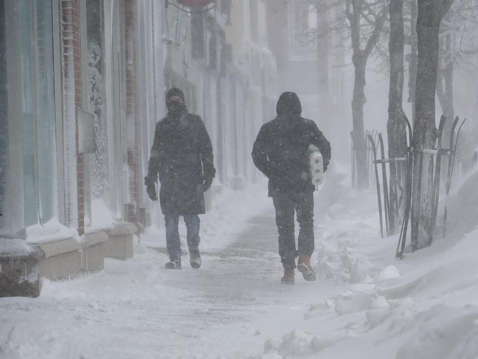 Deux passants marchent dans la tempête au centre-ville de Rimouski.