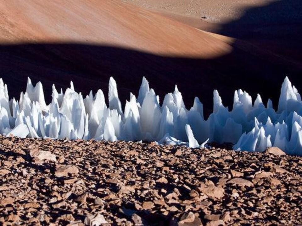 On voit des formations de glace en forme de pics, formant une bande horizontale, au sol. Le reste du terrain est rocheux.