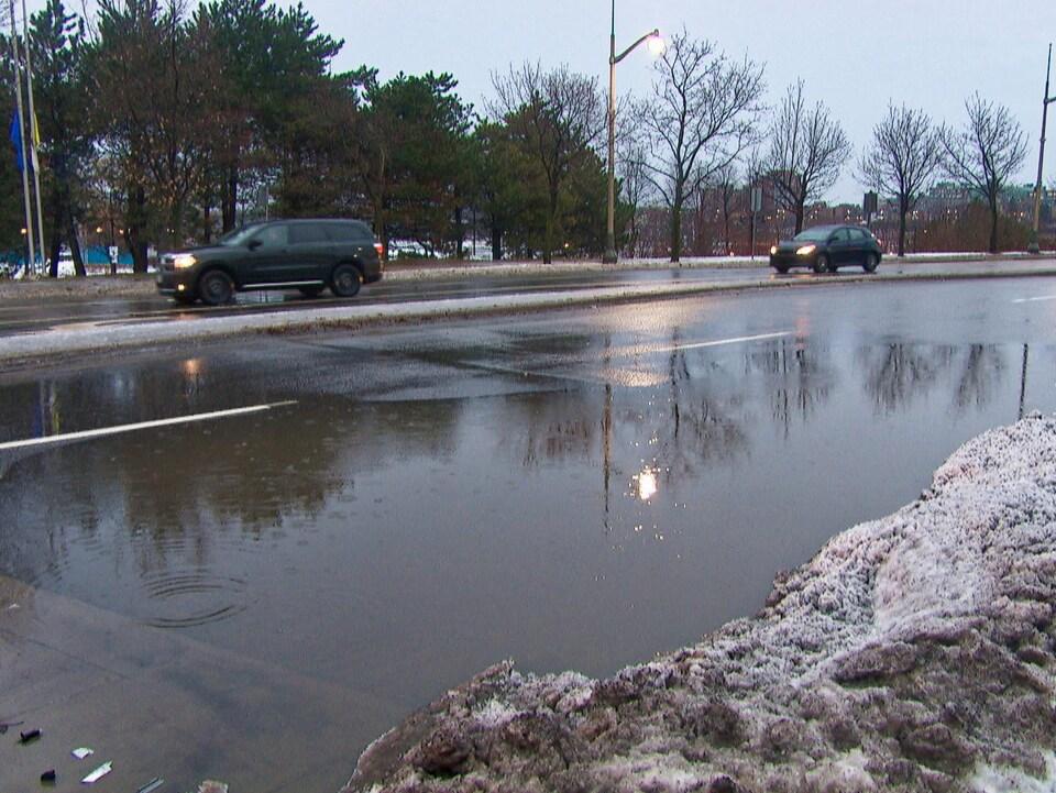 Une flaque d'eau occupe toute une voie d'une rue de Gatineau. Des voitures circulent dans l'autre voie.