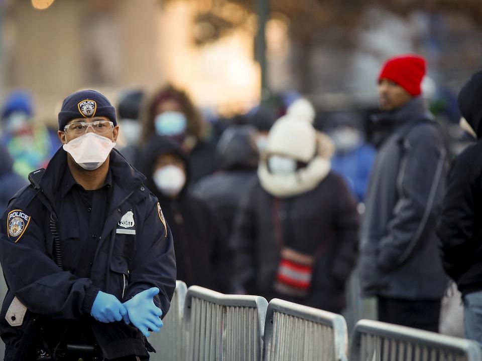 Un policier masqué porte des gants de latex.