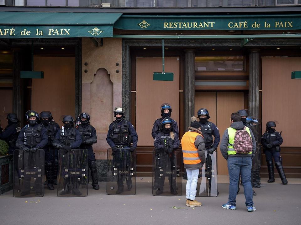 Des policiers antiémeutes se tiennent debout, alignés devant un café fermé à Paris.