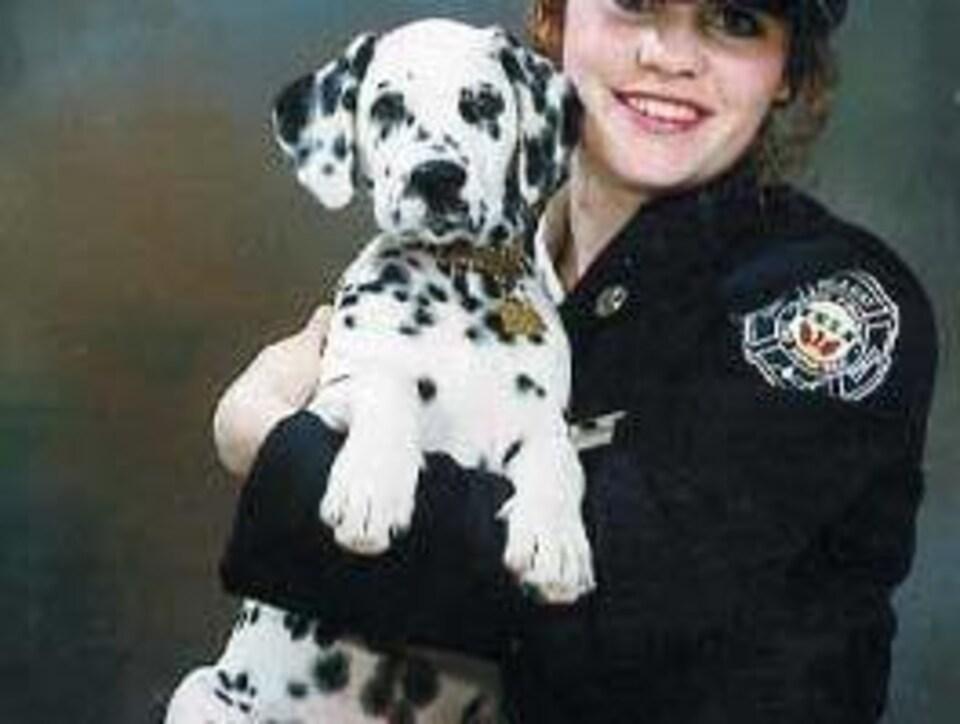 Une pompière tient son chien dalmatien.