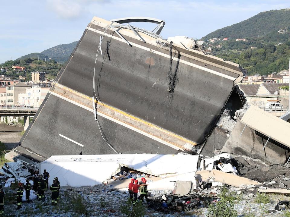 Des secouristes et des pompiers fouillent les décombres du pont Morandi.
