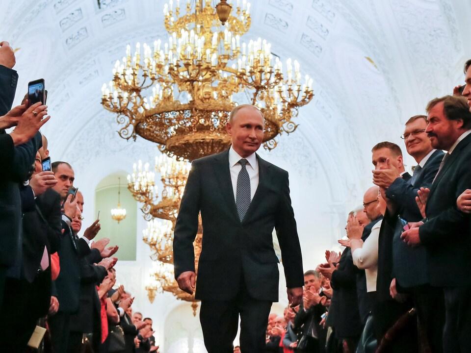 Vladimir Poutine marche entre deux rangées de personnes qui l'applaudissent.