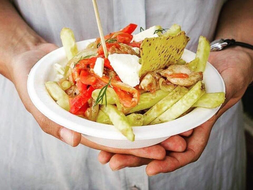 Une personne tient entre ses mains un bol de poutine garnie de poulet, poivrons et tomates.