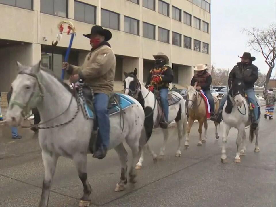 Des autochtones à cheval dans une rue de Winnipeg.